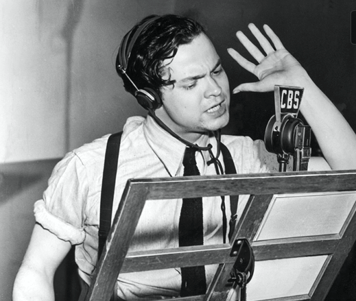 Orson Welles acting for radio with hand raised in front of microphone